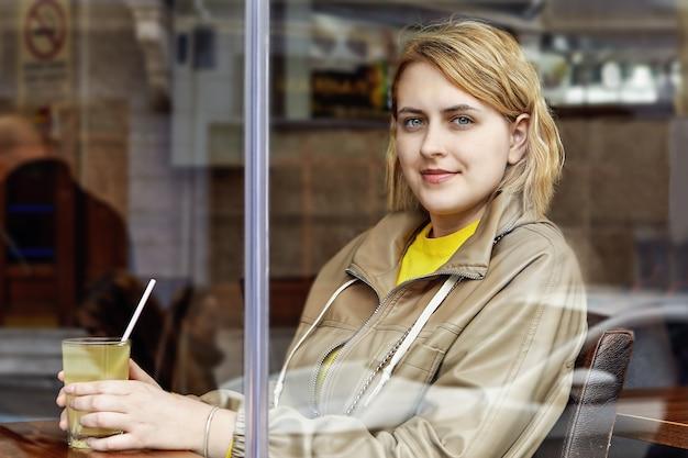 ストローを手にジュースのガラスを保持しているカフェ内の美しいヨーロッパの若い女性の窓からの眺め。 Premium写真