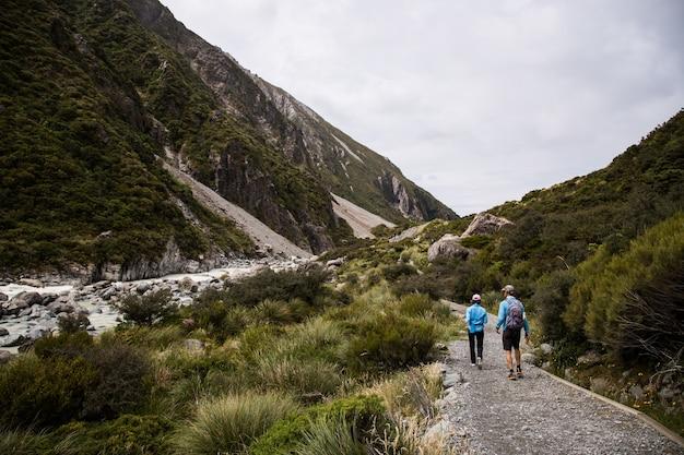 Vista di due persone che fanno un'escursione nelle scogliere coperte di alberi con un fiume tra le scogliere Foto Gratuite