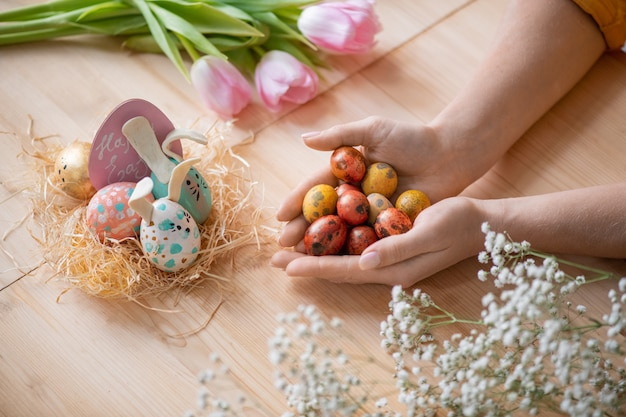Above view of unrecognizable woman holding handful of quails eggs at wooden table while preparing easter eggs for decorations Premium Photo