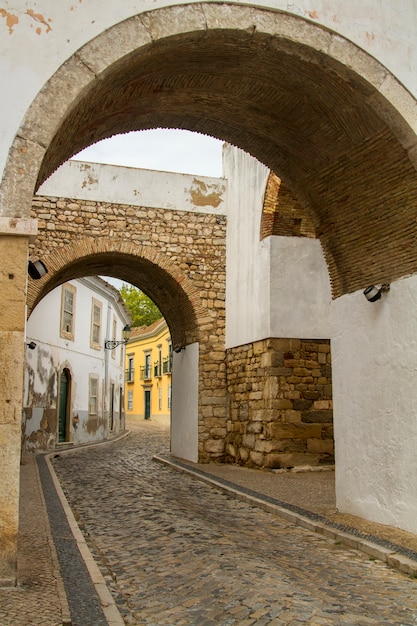 View of the well known arch entrance of faro city, portugal. Premium Photo