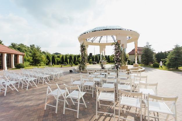 Vista delle sedie bianche dell'ospite e dell'arco cerimoniale decorato all'aperto il giorno soleggiato Foto Gratuite