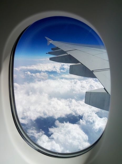 View of the wing of a passenger plane from the porthole in the sky Premium Photo