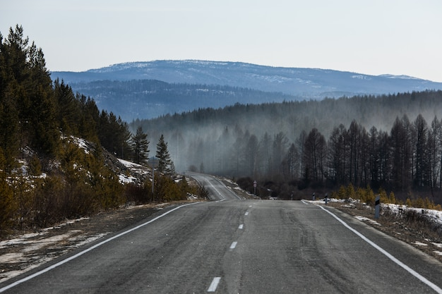 View of the winter road in the mountains with smoke over the forest. forest fire concept Premium Photo