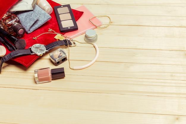 View on women bag stuff on wooden surface Premium Photo