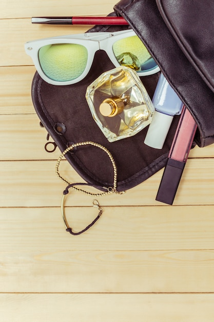View on women bag stuff on wooden Premium Photo