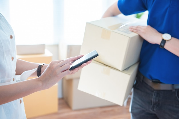 View of young asian woman appending signature in digital smart mobile phone after receiving parcel from courier delivery man at home.ai technology transportation concept. Premium Photo