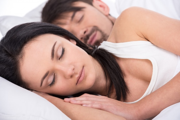 View of a young happy couple are sleeping in bed. Premium Photo