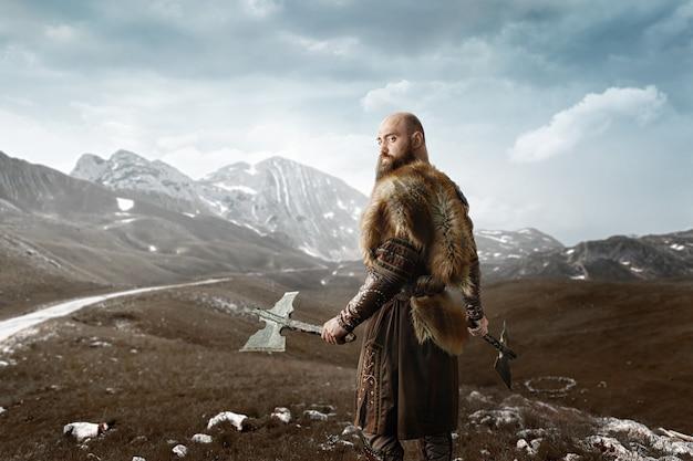 Викинг с топорами в руках у скалистых гор Premium Фотографии