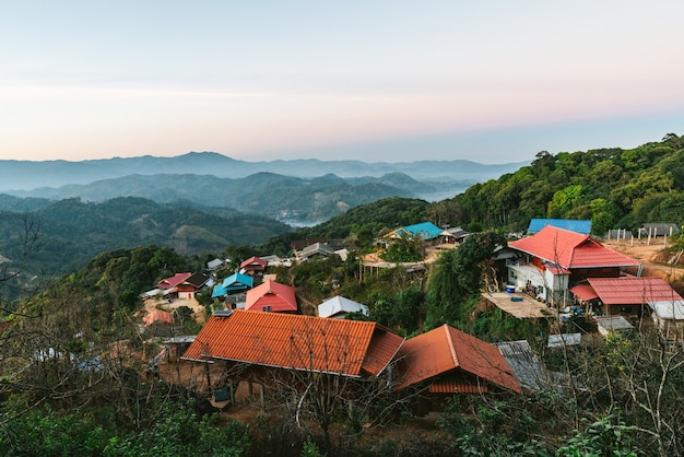 Village amid layers of mountains with sunlight and fog in the evening Premium Photo