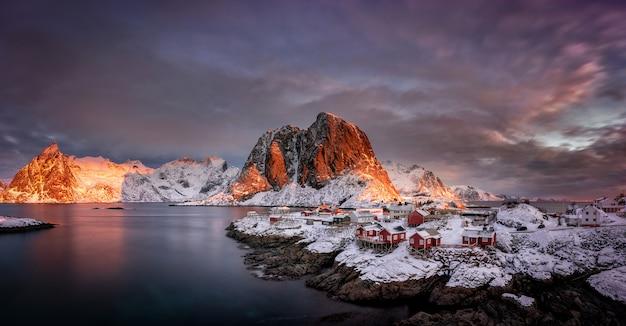 Деревня со снегом и горами в арктике, лофотенские острова в норвегии, скандинавия Premium Фотографии