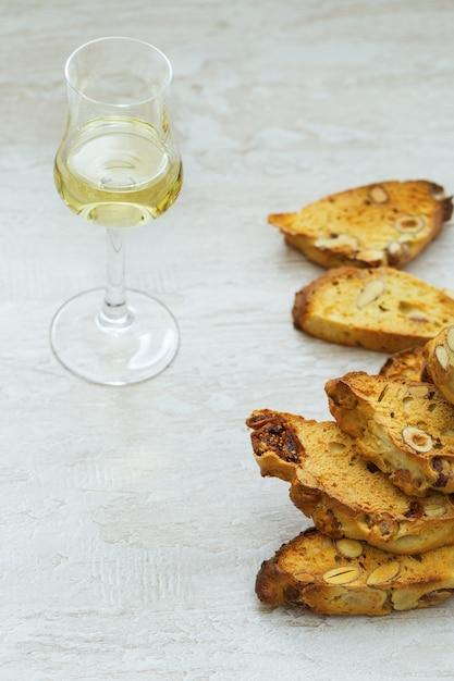 木材の背景に甘いワインvin santoとビスコッティクッキー。甘いワインとデザートのビスコッティのグラス。 Premium写真