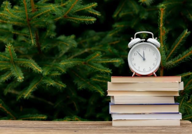 Старинный будильник и книги на деревянный стол с еловыми ветками на фоне Premium Фотографии