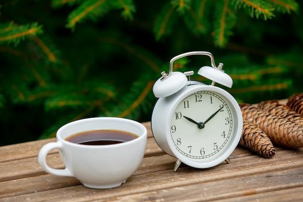 Старинный будильник и чашка кофе на деревянный стол с еловыми ветками на фоне Premium Фотографии