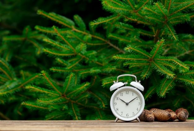 Урожай будильник и сосновые шишки вокруг на деревянный стол с еловыми ветками на фоне Premium Фотографии