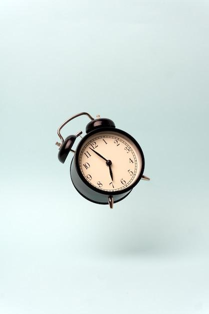 Vintage alarm clock on a blue clean background. Premium Photo