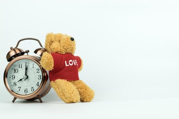 Vintage alarm clock and a little teddy bear Premium Photo