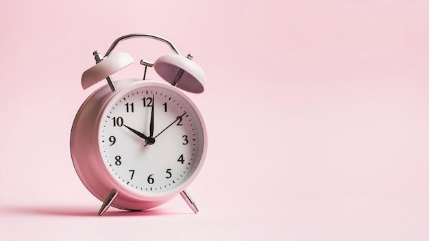 Vintage alarm clock on pink background Free Photo