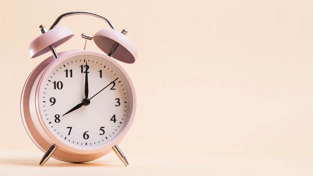 Vintage alarm clock showing 8'o clock time against beige background Free Photo