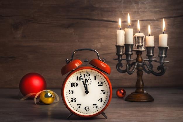Vintage alarm clock showing five to twelve and christmas baubles Premium Photo
