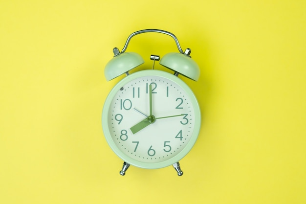 Vintage alarm clock on sweet pastel colored paper Premium Photo