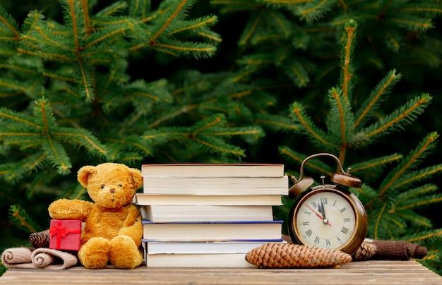 Старинный будильник, плюшевый мишка и книги на деревянный стол с еловыми ветками на фоне Premium Фотографии