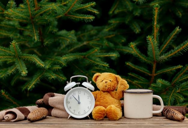 Старинный будильник, плюшевый мишка и чашка кофе на деревянный стол с еловыми ветками на фоне Premium Фотографии