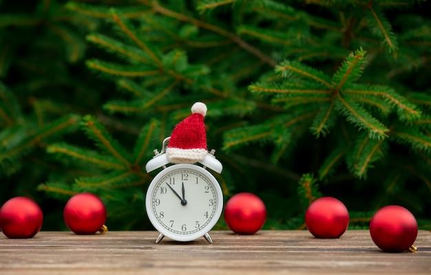 Урожай будильник с рождеством шляпу и безделушки на деревянный стол с еловыми ветками на фоне Premium Фотографии