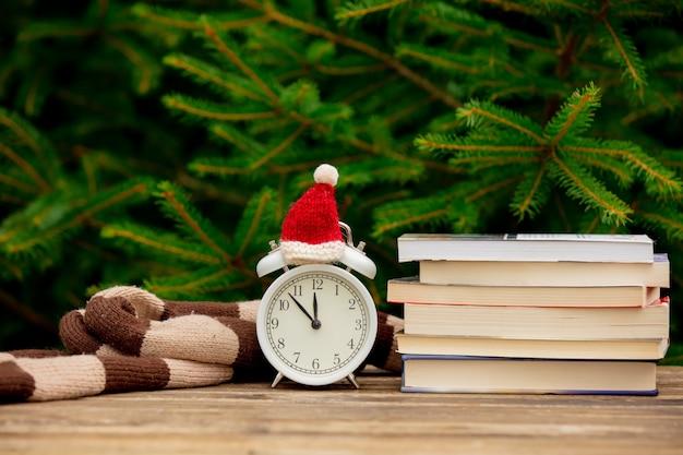Старинный будильник с рождественской шляпой и книгами на деревянном столе с еловыми ветками на фоне Premium Фотографии