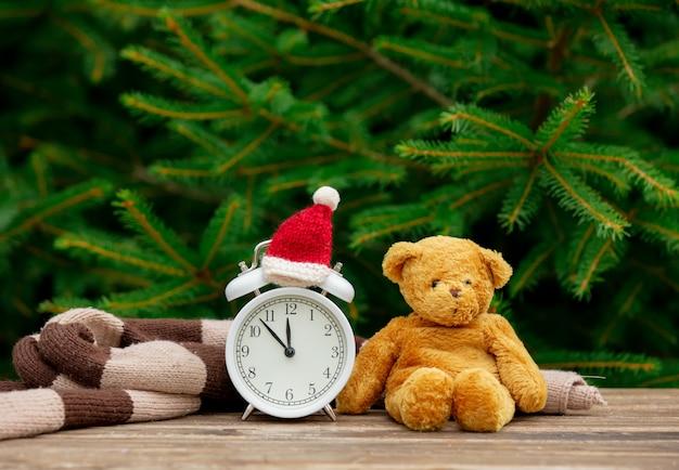 Старинный будильник с рождественской шляпой и плюшевым мишкой на деревянном столе с еловыми ветками на фоне Premium Фотографии