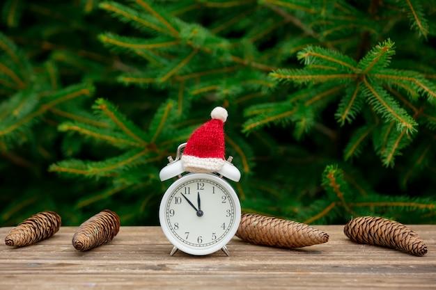 Старинный будильник с рождественской шляпой на деревянном столе с еловыми ветками на фоне Premium Фотографии