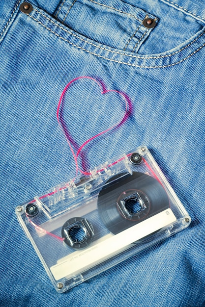 ハートの形として引き出された赤いテープとブルージーンズのヴィンテージオーディオカセット Premium写真