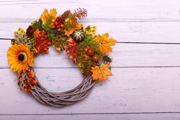 Vintage autumn wreath from leaves and flowers on shabbi wooden backgorund with copy Premium Photo