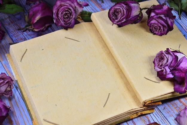 乾燥した芽と写真アルバムのヴィンテージの美しい写真。人生のもろさ。あなたのテキストのための場所を持つクラフト紙の空白のフォトアルバム。 Premium写真