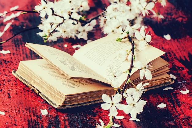 Винтажная библия с цветущей ветвью Premium Фотографии