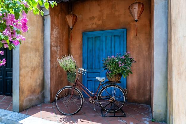 Винтажный велосипед с корзиной, полной цветов рядом со старым зданием в дананге Premium Фотографии