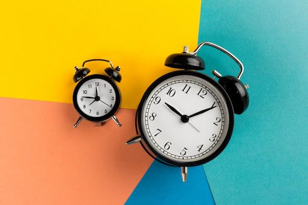Vintage black alarm clock on colorful paper Premium Photo
