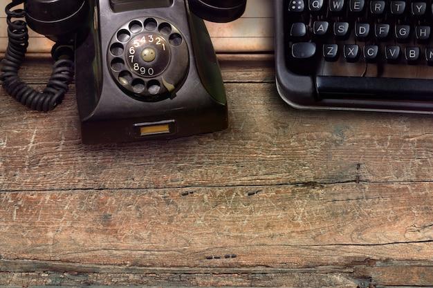 Vintage black phone and typewriter on wooden table background Premium Photo