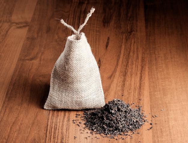 Урожай мешковины с чаем на деревянном фоне Premium Фотографии