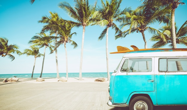 Vintage car parked on the tropical beach with a surfboard on the roof Premium Photo