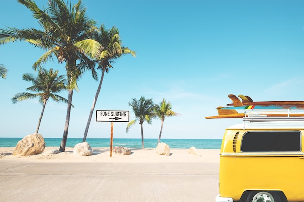 Vintage car with surfboard on roof on tropical beach in summer. beach sign for gone surfing. Premium Photo