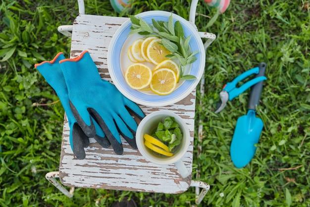 ビンテージの椅子、剪定はさみ、道具、手袋、ミントとレモンのフレッシュハーブティーのカップ Premium写真