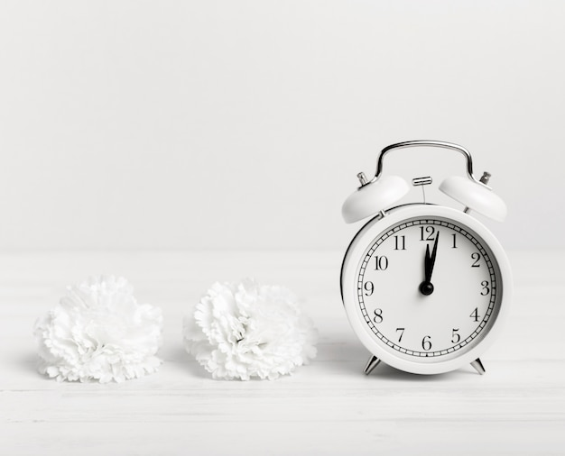 Vintage clock with white flowers beside Free Photo