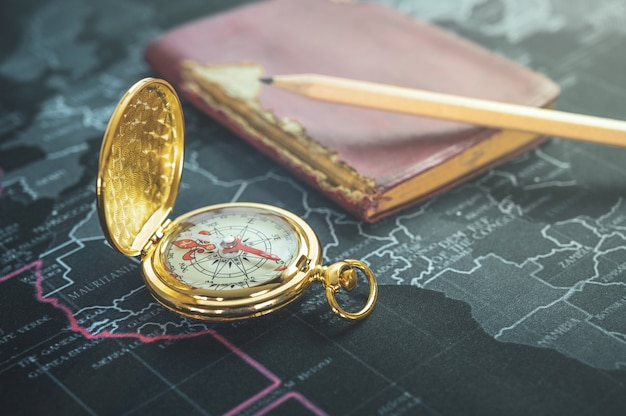 Vintage compass , old notebook, pencil on modern world map Premium Photo