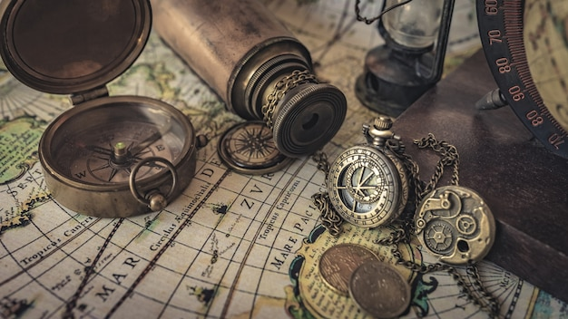 Vintage compass, watch pendant and telescope on old world map Premium Photo