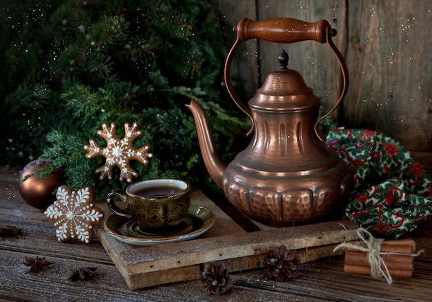 Vintage copper coffee pot, cup of black coffee and christmas gingerbread. Premium Photo