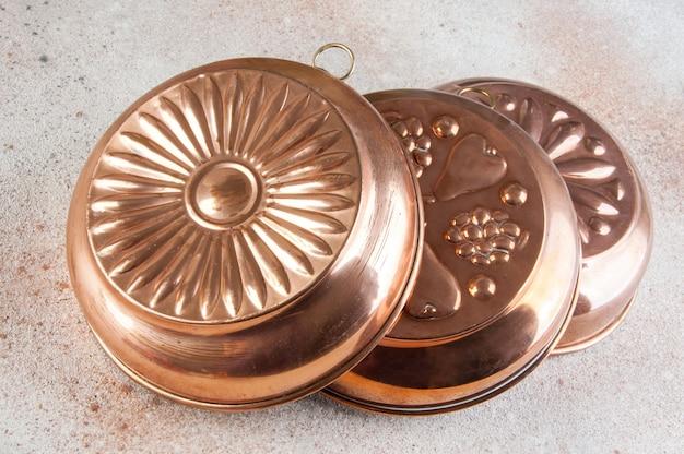 Vintage copper molds on a concrete background. Premium Photo
