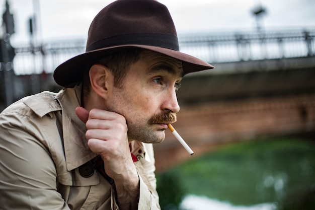Vintage detective smoking a sigarette and looking depressed Premium Photo