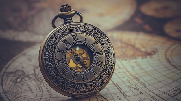 Vintage engraved metal watch face pendant necklace on old world map Premium Photo