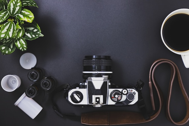 Vintage film cameras and film rolls, black coffee, trees placed on a black background Premium Photo