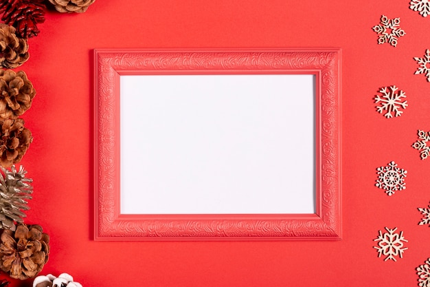 Vintage frame and snowflakes on red table Free Photo